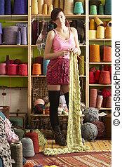 mulher jovem, tricotando, echarpe, ficar, frente, fio, exposição