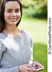 mulher jovem, usando, dela, cellphone, enquanto, ficar, em, um, parque, e, olhando câmera