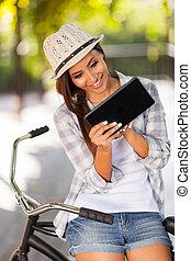 mulher jovem, usando, tabuleta, computador, ao ar livre