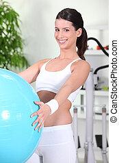 mulher jovem, usando, um, exercite-se bola