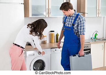 mulher, lavando, mostrando, dano, máquina, repairman