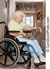 mulher, ligado, cadeira rodas, usando computador portátil