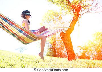 mulher, ligado, rede, lendo um livro, em, primavera