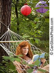 mulher, ligado, um, rede, cercado, por, árvores