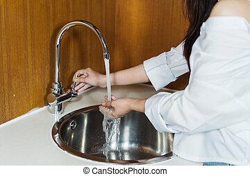 mulher, mãos lavando, em, cozinha