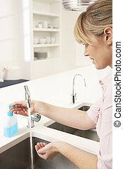 mulher, mãos lavando, em, pia cozinha