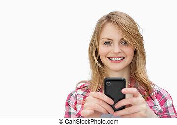 mulher, móvel, olhar, telefone, enquanto, câmera, usando, sorrindo