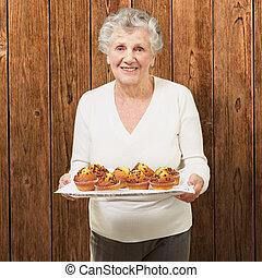 mulher, madeira, mostrando, contra, parede, caseiro, retrato, muffins, sênior