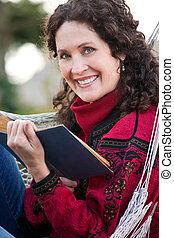 mulher madura, lendo um livro