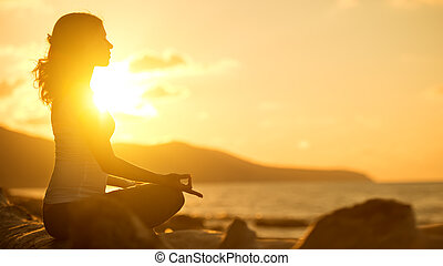 mulher meditando, em, pose lotus, ligado, praia, em, pôr do sol