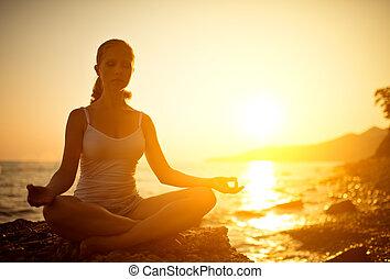 mulher meditando, em, pose lotus, praia, em, pôr do sol