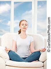 mulher meditando, relaxante, sentando, em, um, posição lotus, sofá, casa, contra, a, janela, e, a, céu