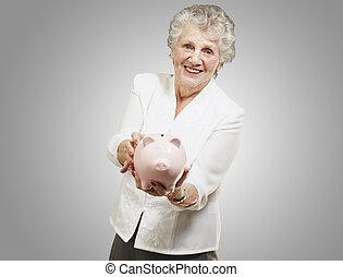 mulher, mostrando, cinzento, piggy, fundo, retrato, sênior, sobre, banco