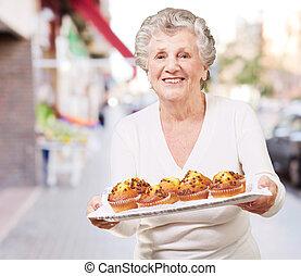 mulher, muffin, mostrando, chocolate, rua, retrato, sênior, bandeja