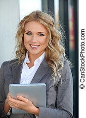 mulher negócios fica, exterior, com, eletrônico, tabuleta