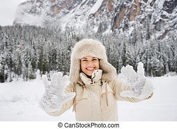 mulher, neva-coberto, agasalho, mostrando, ao ar livre, chapéu pele, mittens