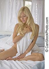 mulher nua, sentar-se cama, olhando baixo