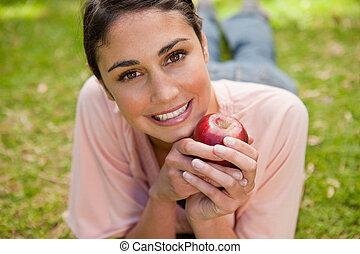 mulher olha, à frente, enquanto, segurar uma maçã
