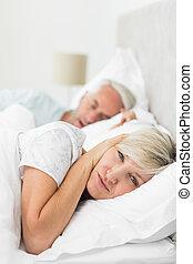 mulher, orelhas covering, enquanto, homem, roncar, cama