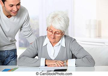 mulher, paperwork, jovem, idoso, ajudando, homem