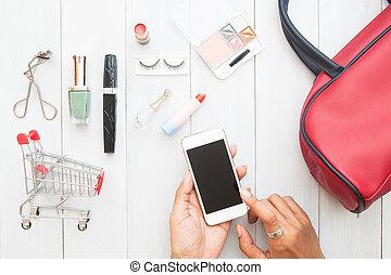 mulher, passe tocar tela, ligado, móvel, dispositivo, com, carro shopping, e, cosméticos, ligado, madeira, fundo, criativo, apartamento, configuração, shopping linha, conceito