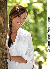 mulher, peeking, detrás, um, árvore