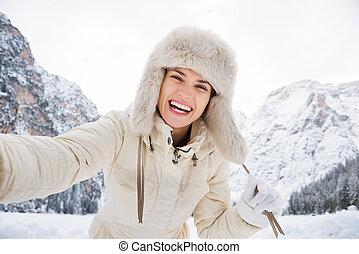mulher, pele, casaco inverno, levando, ao ar livre, chapéu branco, selfie