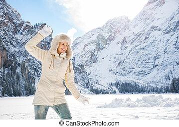 mulher, pele, jogar, agasalho, neve bola, ao ar livre, chapéu, feliz