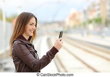 mulher, percorrendo, social, mídia, em, um, treine estação