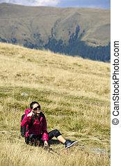 mulher, polegar, câmera, mochila, lado montanha, cima, jovem, carregar, retrato, mostrando