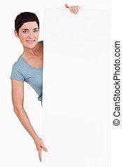 mulher, posar, atrás de, um, em branco, painel