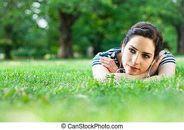 mulher relaxando, jovem, escutar música, ao ar livre