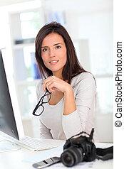 mulher, repórter, foto, sentando, jovem, computador desktop, frente