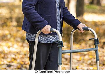 mulher sênior, andar, com, caminhante, em, outono, parque