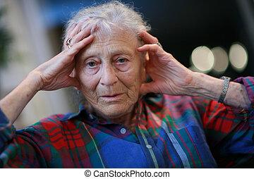 mulher sênior, cabeça, segurando