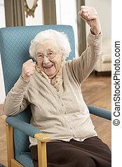 mulher sênior, celebrando, cadeira, casa