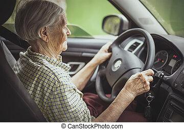 mulher sênior, dirigindo um carro