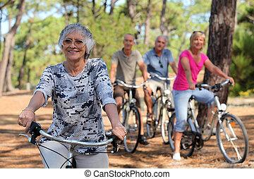 mulher sênior, e, dela, amigos, bicicletas equitação, através, a, campo