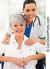mulher sênior, em, cadeira rodas, com, caregiver