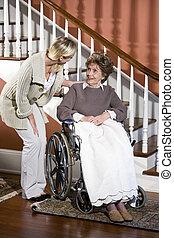 mulher sênior, em, cadeira rodas, com, enfermeira, ajudando