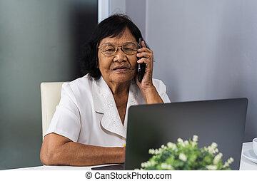 mulher sênior, falando telefone móvel, e, usando computador portátil