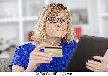 mulher sênior, fazendo compras online