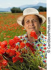 mulher sênior, flores colheita, ligado, a, papoula, campo