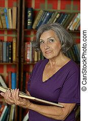 mulher sênior, leitura, em, biblioteca