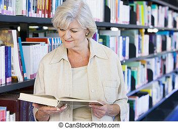 mulher sênior, leitura, em, um, biblioteca