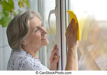 mulher sênior, limpeza janela