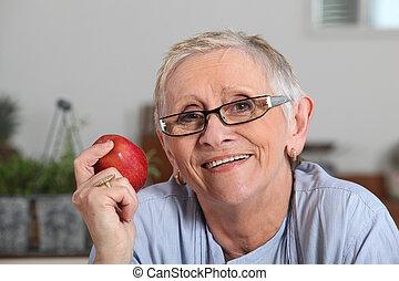 mulher sênior, maçã, mão