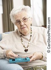 mulher sênior, ordenando, medicação, usando, organizador, casa