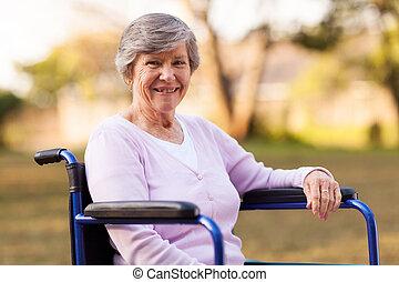 mulher sênior, sentando, ligado, cadeira rodas, ao ar livre