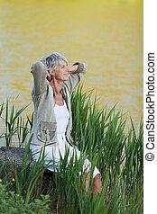 mulher sênior, sentando, perto, um, lago, para, fresco,...